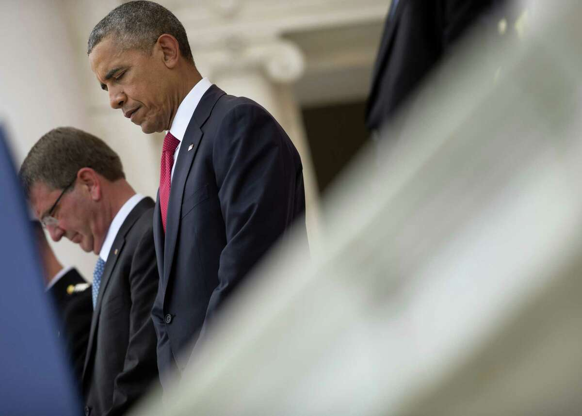 President Barack Obama with Defense Secretary Ash Carter, left, in the Memorial Amphitheater at Arlington National Cemetery in Arlington, Va., Monday, May 30, 2016, during a Memorial Day ceremony.