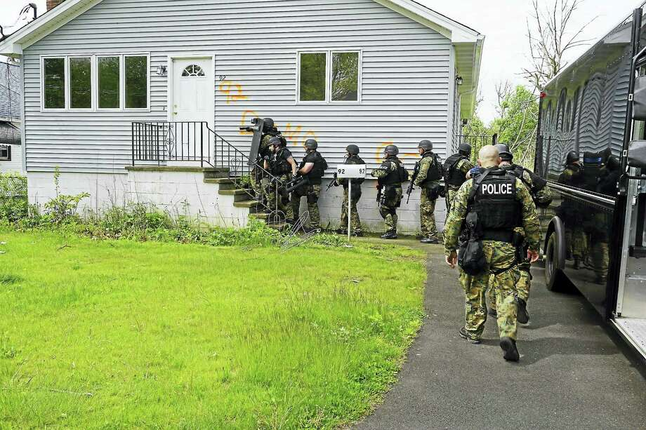 The West Haven Fire Department and the West Haven Police Department SWAT Team practice on one of the houses slated for demolition in the Old Field Creek area as part of a federally-funded emergency watershed protection program that aims to remove homes with repetitive flood issues. Photo: Photo By Eileen Krugel, City Of West Haven