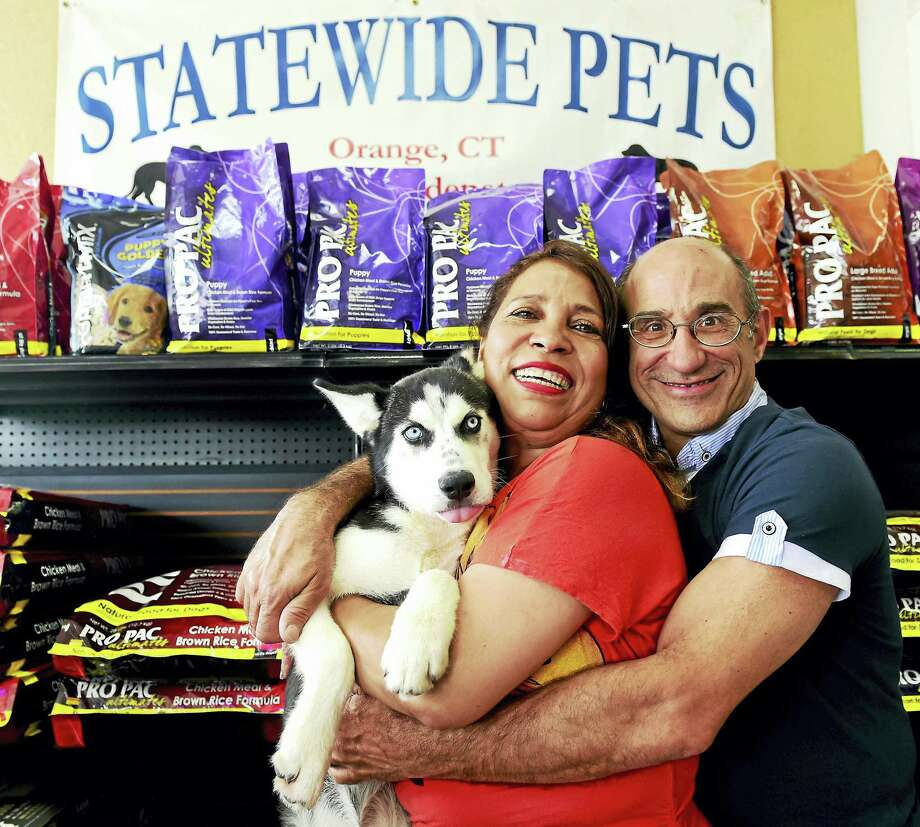 (Peter Hvizdak - New Haven Register)  Carmen Primus and Steve Primus of Statewide Pets in Orange with a Siberian Huskie in their pet store Thursday. Photo: ©2016 Peter Hvizdak / ©2016 Peter Hvizdak