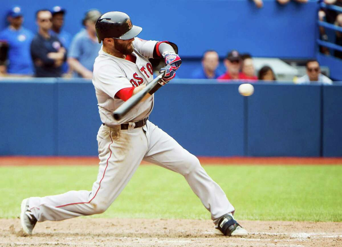 Dustin Pedroia hits an RBI double against the Jays during the 11th inning on Sunday.
