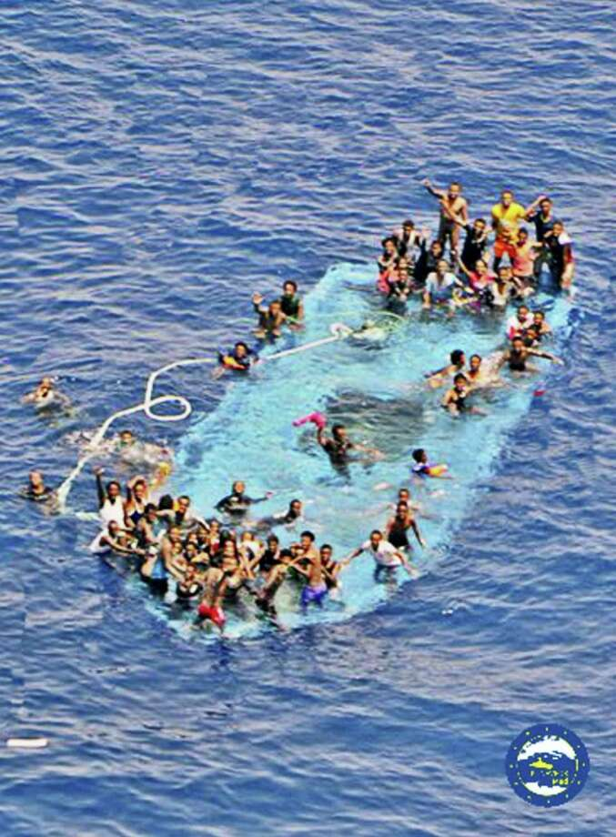 People ask for help after their boat overturned off the Libyan coast on May 26, 2016. A migrant boat sank off Libya's coast Thursday with about 100 passengers on board. Officials said 88 people had been rescued and that some 20 bodies were spotted in the sea. Photo: EUNAVFORMED Via AP   / EUNAVFORMED
