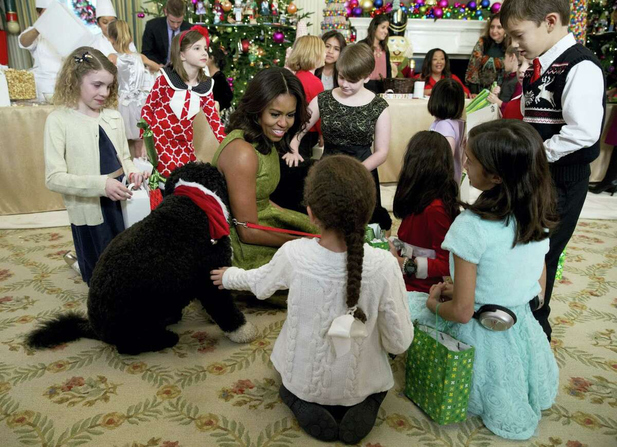 In this Dec. 2, 2015 photo, first lady Michelle Obama with dogs Bo, left, and Sunny, behind at right, are surrounded by children in the State Dining Room of the White House in Washington, where they made holiday crafts and treats during a preview of the 2015 White House holiday decor.