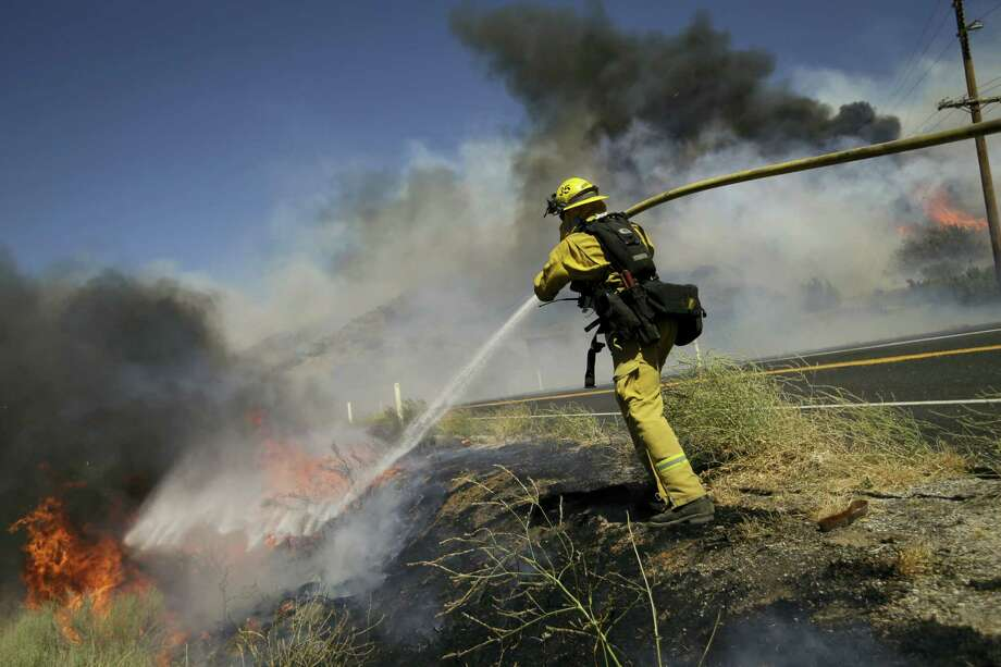 A firefighter puts out a wildfire burning along Highway 178 near Lake Isabella, Calif. The wildfire that roared across dry brush and trees in the mountains of central California gave residents little time to flee as flames burned homes to the ground, propane tanks exploded and smoke obscured the path to safety. Photo: AP Photo — Jae C. Hong    / Copyright 2016 The Associated Press. All rights reserved. This material may not be published, broadcast, rewritten or redistribu