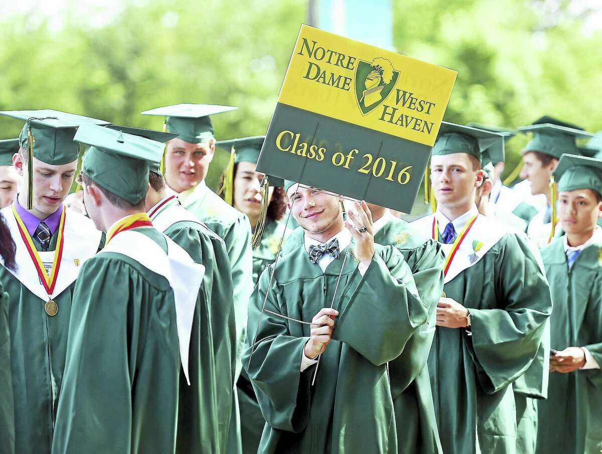 Cal Motasky lifts a lawn sign advertising the Notre Dame West Haven Class of 2016 as the class walks into graduation exercises in West Haven.
