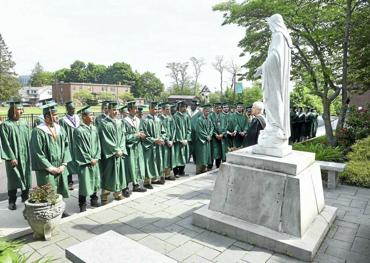 Notre Dame West Haven graduates recite Pray For Us in front of the statue of the Blessed Virgin Mary as they walk into graduation exercises in West Haven. Arnold Gold-New Haven Register