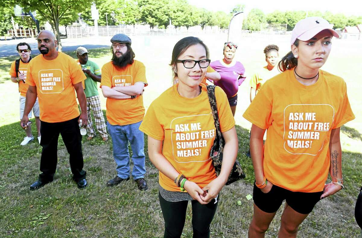 Mona Liu, center, and Hailey O'Brien, right, of Southern Connecticut State University listen to speakers during the kickoff for New Haven's Free Summer Meals program at Goffe Park in New Haven on Saturday.