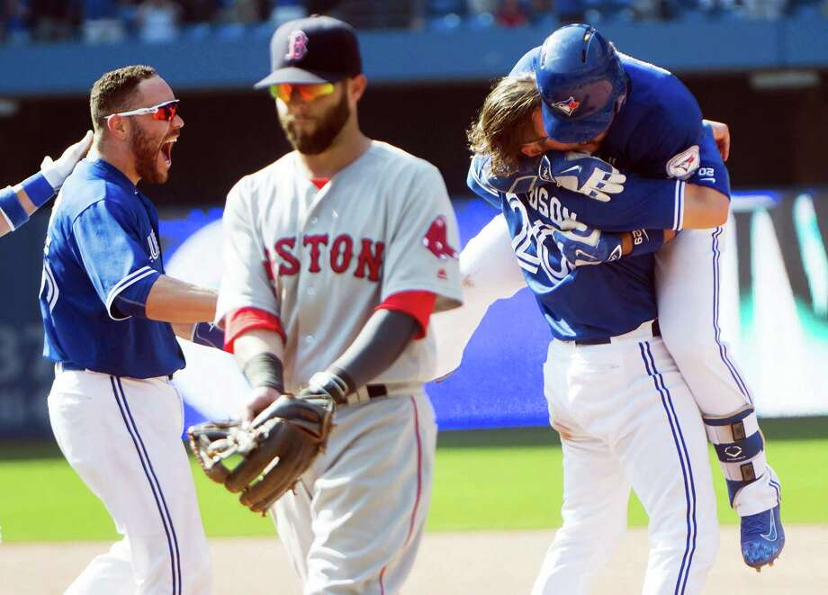 Josh Donaldson, second from right, and Russell Martin, left, rush Devon Travis after Travis drove in the game-winning run. In the foreground is Red Sox second baseman Dustin Pedroia. Photo: Nathan Denette — The Canadian Press Via AP   / cp