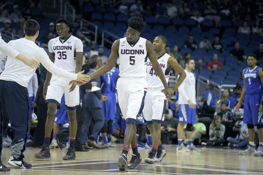 UConn's Daniel Hamilton is congratulated by teammates during a game last season. Photo: The Associated Press File Photo   / FR121174 AP