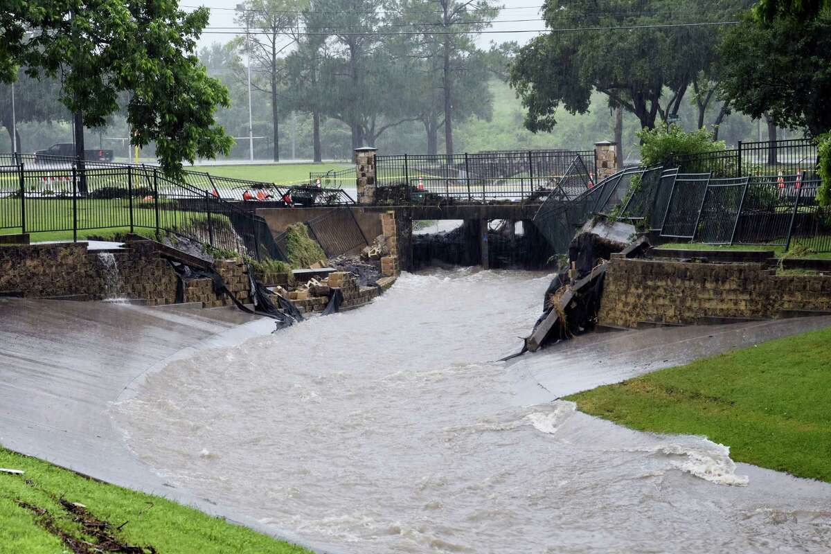 Water rushes down a canal under the washed out bridge at North Park Street in Fireman's Park as heavy rain falls, Friday, May 27, 2016, in Brenham, Texas.