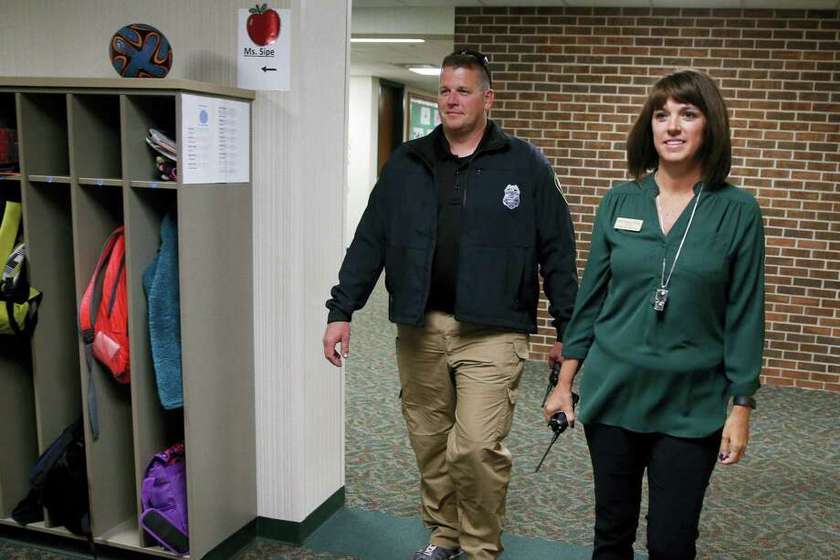 In this May 6, 2016, Forest Dale Elementary School principal Deanna Pitman, right, and Carmel, Ind., police officer Greg DeWald walk the halls of the school during an intruder drill at the school in Carmel, Ind. Pitman posed as an intruder for the drill. More and more, schools these days are conducting active-shooter drills. A government report found that more than two-thirds of the school districts surveyed conduct active shooter exercises. Photo: AP Photo/Michael Conroy    / Copyright 2016 The Associated Press. All rights reserved. This material may not be published, broadcast, rewritten or redistribu