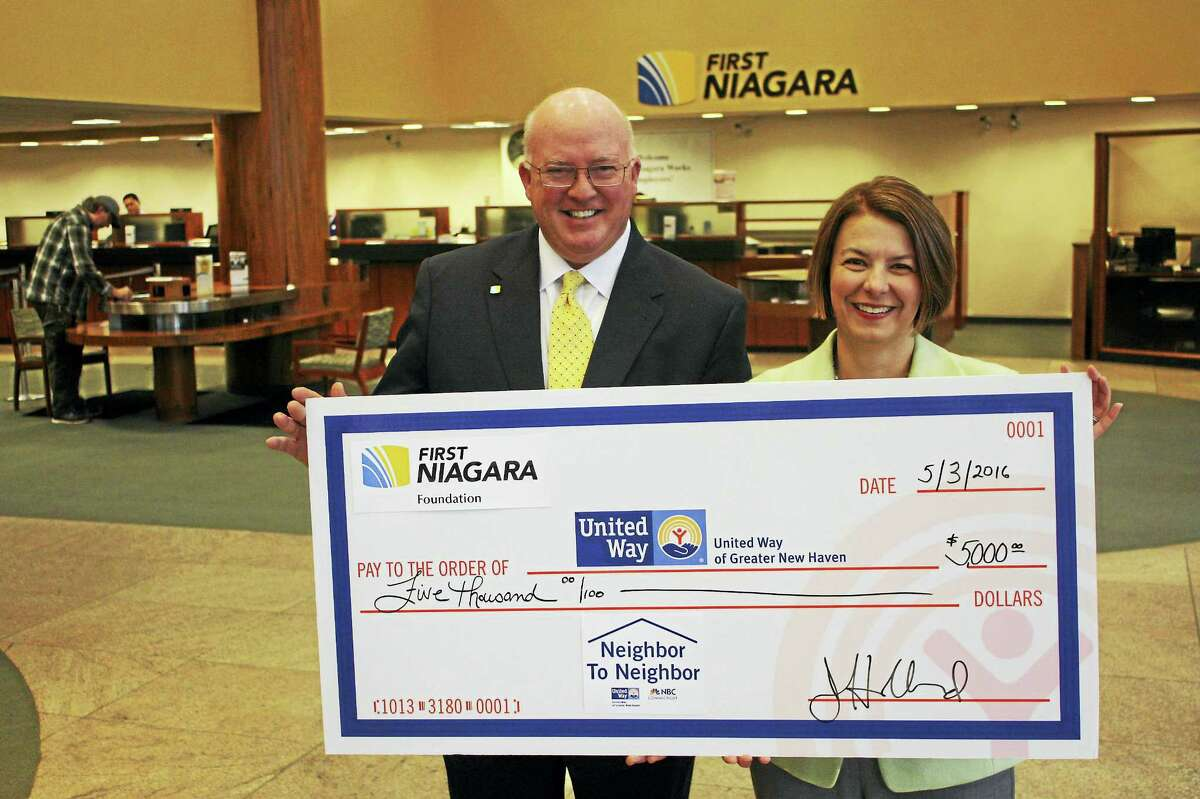 """AIDING THE UNITED WAY: First Niagara New England Region President Jeff Hubbard, left, and Jennifer Heath, incoming president & CEO of United Way of Greater New Haven, with a donation of $5,000 from First Niagara Foundation, the not-for-profit charitable entity of First Niagara Bank, to the United Way of Greater New Haven's Neighbor to Neighbor campaign. """"First Niagara is a proud supporter of United Way, and its work in our local community,"""" Hubbard said in a release. """"In addition to our annual United Way campaign giving, we are pleased to be able to contribute to the Neighbor to Neighbor program to help address the challenges faced by our most vulnerable community neighbors."""" This year's Neighbor to Neighbor campaign raised $300,000, according to the release. """"We are proud of the new partnerships we've made this year, increasing the visibility of this campaign and the vulnerable population served by it. Every dollar matters, and we are thankful for all of the gifts that came in, big and small."""" Heath said in the release."""
