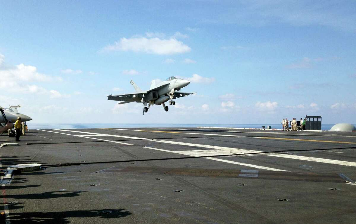 In this Friday, April 15, 2016, file photo, an FA-18 jet fighter lands on the USS John C. Stennis aircraft carrier in the South China Sea while U.S. Defense Secretary Ash Carter visited the aircraft carrier during a trip to the region. (AP Photo/Lolita C. Baldor, File)