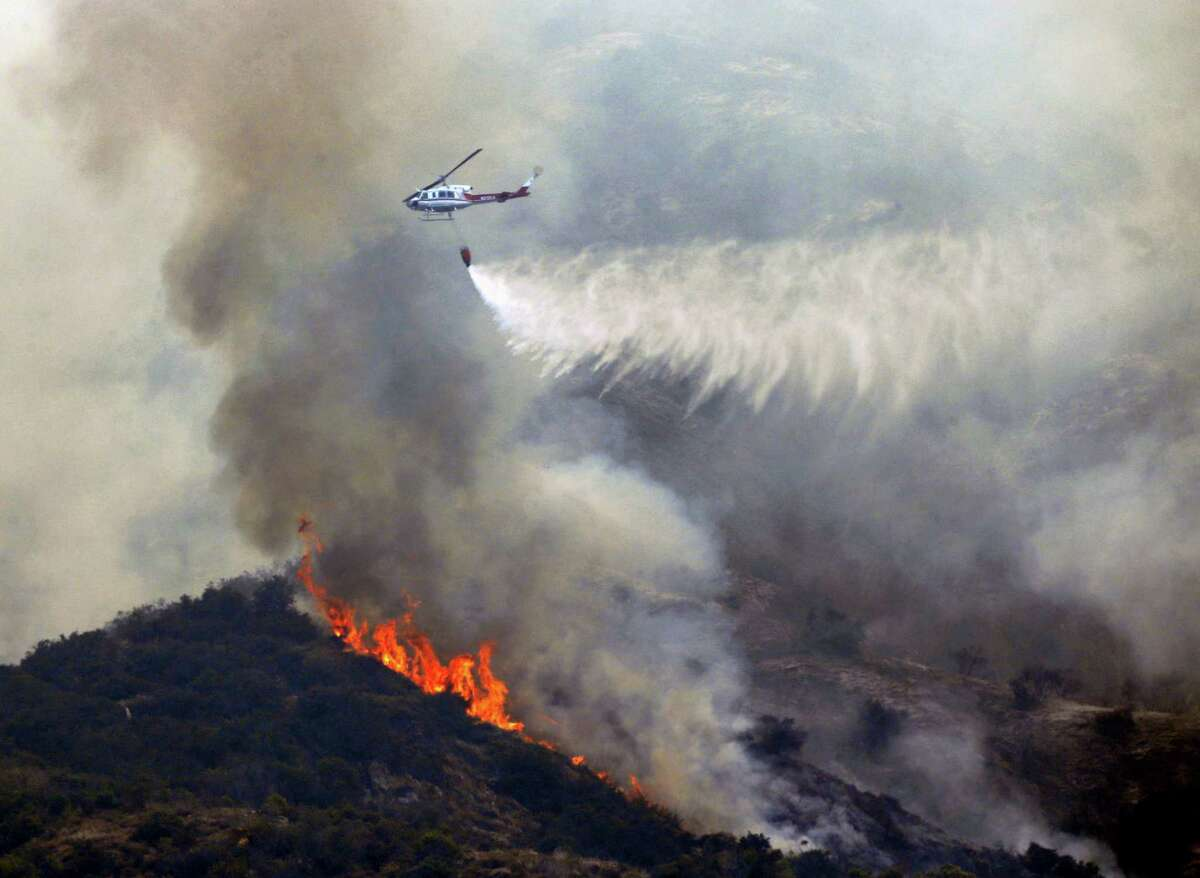 A firefighting helicopter makes a water drop over a wildfire near Bradbury, Calif. on Wednesday, June 22, 2016. Cooler, more humid weather gave at least some temporary help Wednesday to crews battling dangerous wildfires in Southern California, while other blazes across the West were on the move.