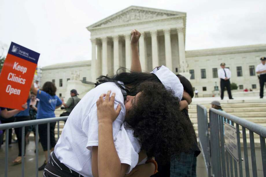 Jackelin Alfaro, 7, of Washington, hugs her aunt Gelin Alfaro, of Veracruz, Mexico, during an immigration rally at the Supreme Court in Washington Thursday. Photo: ASSOCIATED PRESS   / Copyright 2016 The Associated Press. All rights reserved. This material may not be published, broadcast, rewritten or redistribu