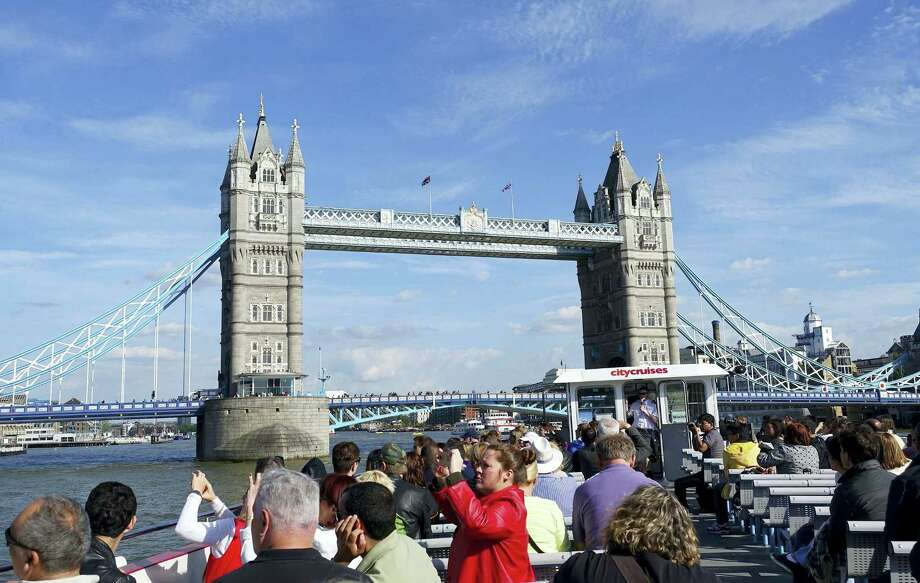 In this May 21, 2015, file photo, a London City Cruises boat tours the River Thames near the Tower Bridge in London. There are plenty of sights to see for families on vacation in London, like the Harry Potter studio tour, Big Ben and the London Eye. The scene was more tense after the Brexit vote Thursday, June 23, 2016, as Londoners reacted with uncertainty and even anger. Photo: AP Photo/Ross D. Franklin    / Copyright 2016 The Associated Press. All rights reserved. This material may not be published, broadcast, rewritten or redistribu