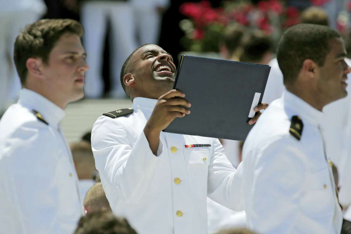 Keenan Reynolds, graduating U.S. Naval Academy Midshipman and the Baltimore Ravens' sixth round NFL draft pick, reacts after receiving his diploma during the Academy's graduation and commissioning ceremony in Annapolis, Md., Friday, May 27, 2016. He will be allowed to defer his service time to play in the NFL.