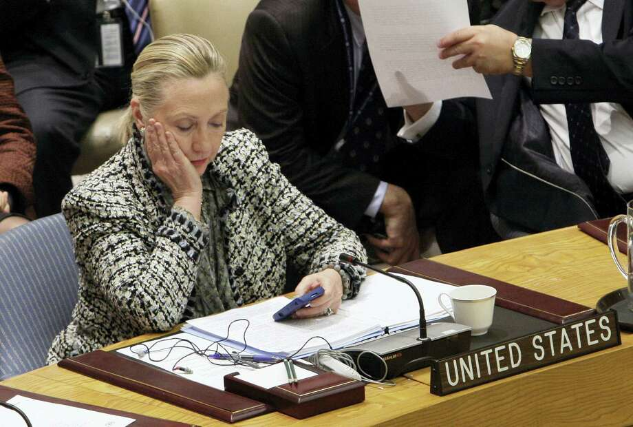 In this March 12, 2012, file photo, then-Secretary of State Hillary Rodham Clinton checks her mobile phone after her address to the Security Council at United Nations headquarters. Newly released emails show State Department staffers wrestled in December 2010 over a serious technical problem with then-Secretary of State Hillary Clinton's home email server. They temporarily disabled security features, which left the server more vulnerable to hackers. Weeks later, hackers attacked the server so seriously it was shut down. Photo: AP Photo/Richard Drew, File    / AP