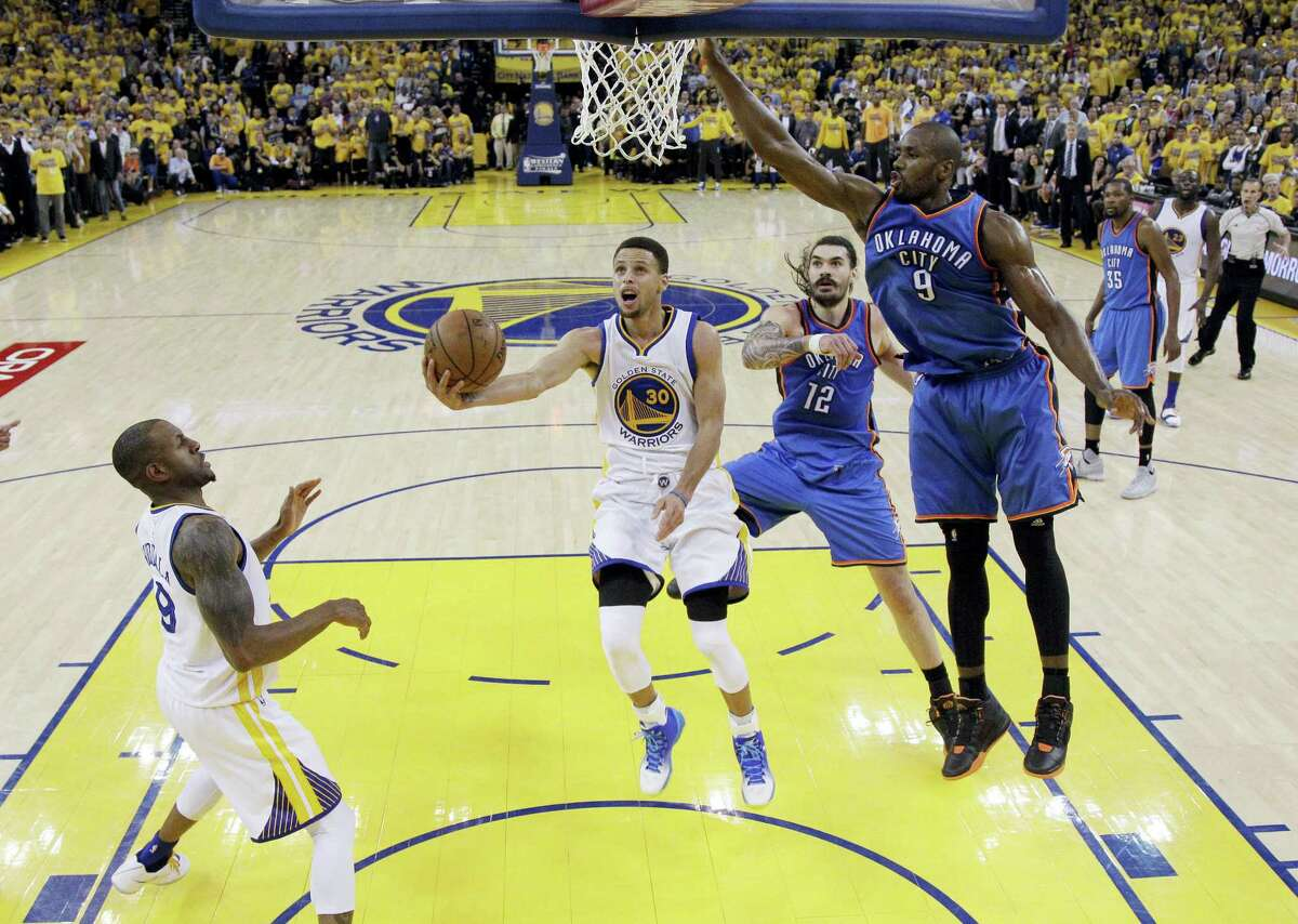 The Warriors' Stephen Curry drives to the basket as the Thunder's Serge Ibaka (9) and Steven Adams (12) defend during the second half of Game 5 on Thursday.