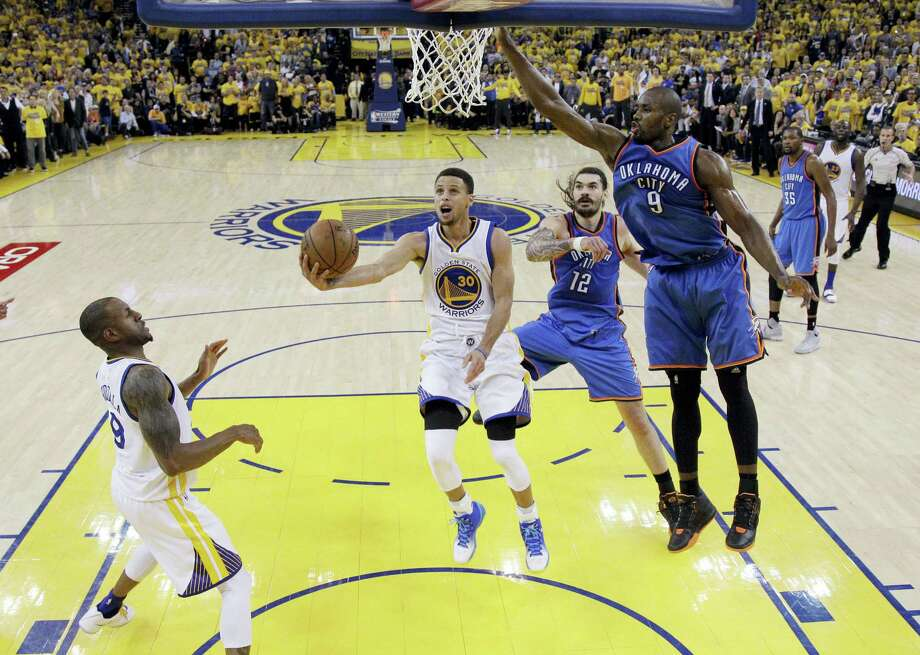 The Warriors' Stephen Curry drives to the basket as the Thunder's Serge Ibaka (9) and Steven Adams (12) defend during the second half of Game 5 on Thursday. Photo: Marcio Jose Sanchez — The Associated Press   / AP