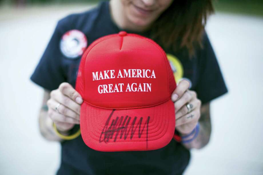 "Diana Noschang, of Newburgh, N.Y., holds a ""Make America Great Again"" hat autographed by Republican presidential candidate Donald Trump. Photo: The Times & Tribune Via AP   / The Scranton Times-Tribune"