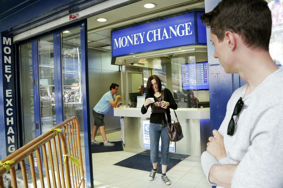 """Claire Hunt, center, of Reading, England, changes pounds for dollars, Friday, June 24, 2016, at a money exchange in New York. Britain voted to leave the European Union after a bitterly divisive referendum campaign, toppling the government Friday, sending global markets plunging and shattering the stability of a project in continental unity designed half a century ago to prevent World War III. """"I think the exchange went down about eight percent (from yesterday),"""" said Hunt, who is vacationing with her son, Jacob Wood, right. """"It's scary. I don't know what we are going home to."""""""