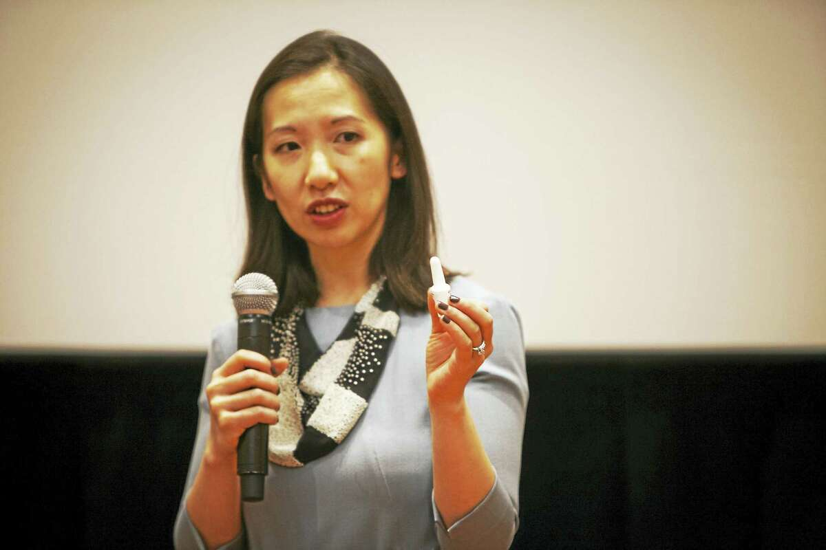 Baltimore City Health Commissioner Dr. Leana Wen holds up a naloxone dispenser while speaking to journalists in Baltimore.