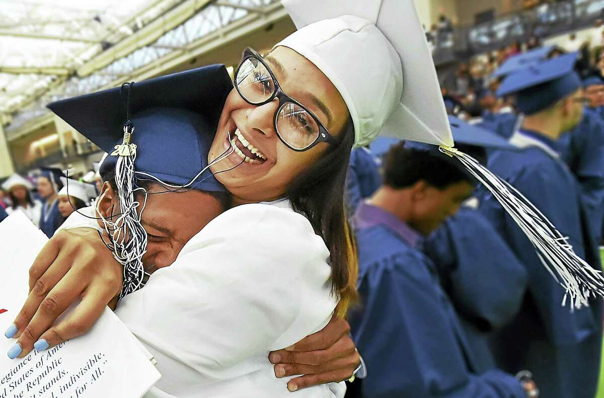 Destiny Garcia and Malik Thorne celebrate with a big hug at the end of graduation at James Hillhouse High School, Thursday, June 16, 2016, at the Floyd Little Athletic Center in New Haven. (Catherine Avalone/New Haven Register)