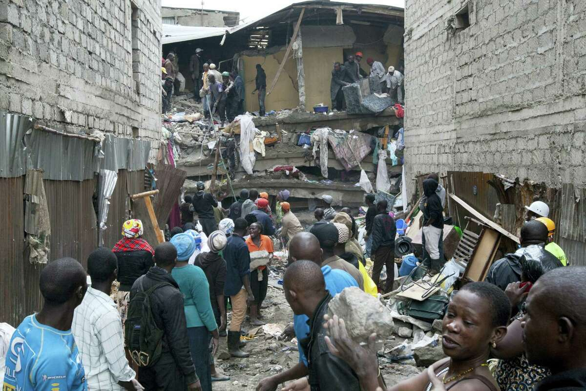 People help survivors retrieve their household items at the site of a building collapse in Nairobi, Kenya, Saturday, April 30, 2016. A six-story residential building in a low income area of the Kenyan capital collapsed Friday night under heavy rain and flooding, killing at least seven people and injuring over 100 others, Kenyan officials said.
