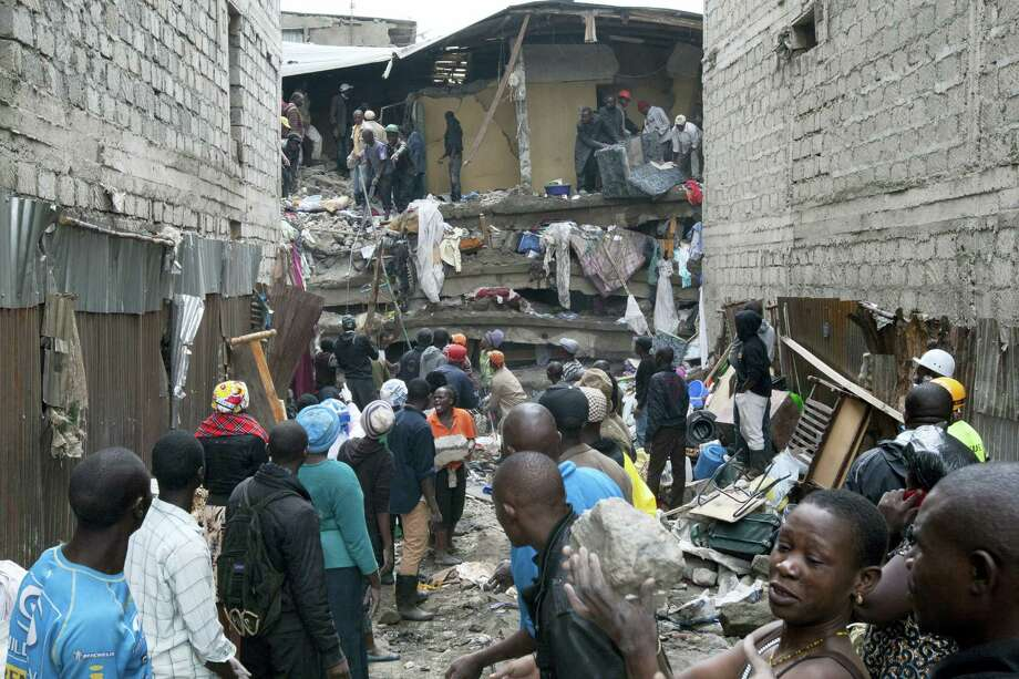 People help survivors retrieve their household items at the site of a building collapse in Nairobi, Kenya, Saturday, April 30, 2016. A six-story residential building in a low income area of the Kenyan capital collapsed Friday night under heavy rain and flooding, killing at least seven people and injuring over 100 others, Kenyan officials said. Photo: AP Photo — Sayyid Abdul Azim / AP
