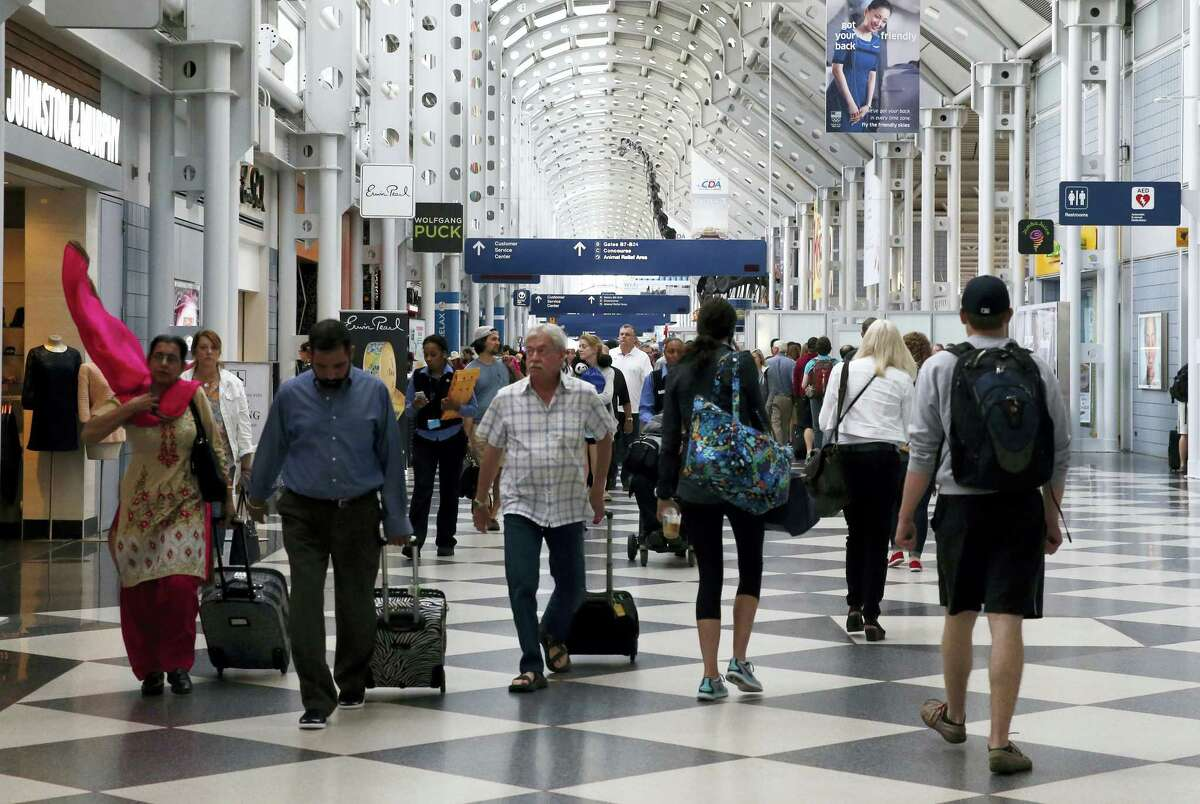 Travelers walk to gates after passing through a Transportation Security Administration checkpoint at O'Hare International Airport, Friday, May 27, 2016, in Chicago. Memorial Day weekend, the unofficial start of summer vacations for many and a busy travel period, serves as a crucial test for the TSA.