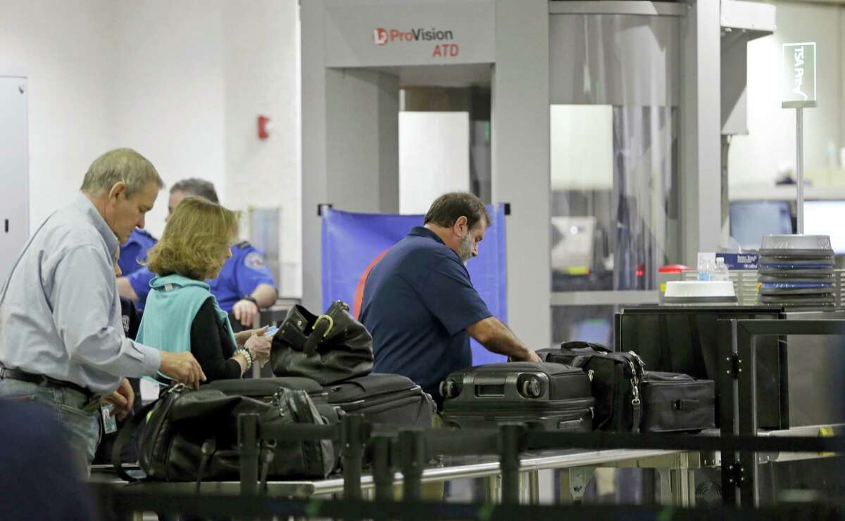 Travelers stand in line as they prepare to put their luggage through an X-ray machine at a Transportation Security Administration checkpoint at Miami International Airport, Thursday, May 26, 2016, in Miami. Memorial Day weekend, the unofficial start of summer vacations for many and a busy travel period, serves as a crucial test for the TSA.
