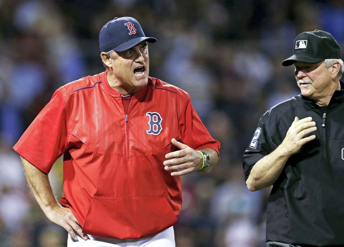 Boston Red Sox manager John Farrell, left, argues with umpire Dana DeMuth, right, during the eighth inning of a baseball game at Fenway Park, Wednesday, June 22, 2016, in Boston. Farrell argued that a ball hit by Chris Young was a home run, but officials disagreed. (AP Photo/Charles Krupa)
