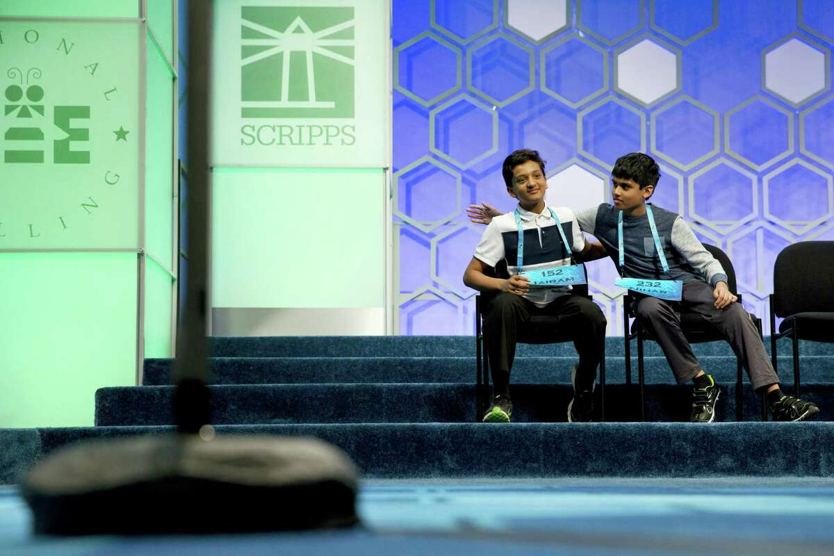 Jairam Hathwar, 13, of Painted Post, N.Y., left, and Nihar Janga, 11, of Austin, Texas, right, pat each other on the back as they hear that they will likely be announced co-champions after a drawn-out battle that did indeed end in them being named co-champions in the 2016 National Spelling Bee, in National Harbor, Md., on Thursday, May 26, 2016.