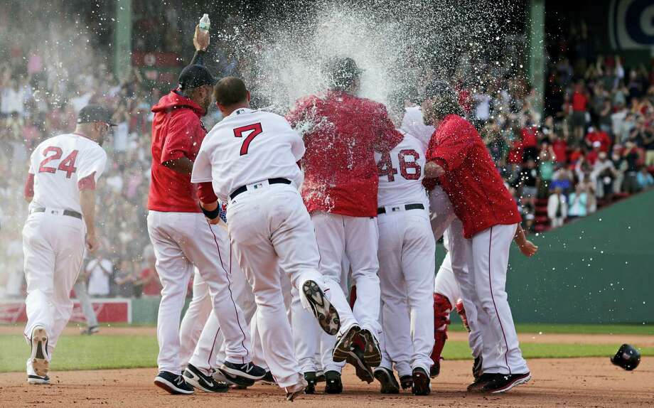 Teammates surround Boston Red Sox's Xander Bogaerts and douse him after his walkoff RBI-single during the 10th inning against the Chicago White Sox at Fenway Park Thursday in Boston. Photo: Charles Krupa — The Associated Press    / AP
