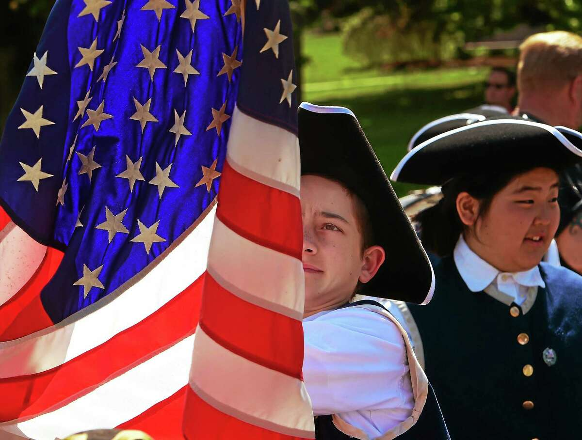 Tucker Sutherland, 12, of the St. Mary's School Fife and Drum Corps of Branford, straightens the American Flag before the start of the Branford Memorial Day Parade on the Branford Green in 2015.