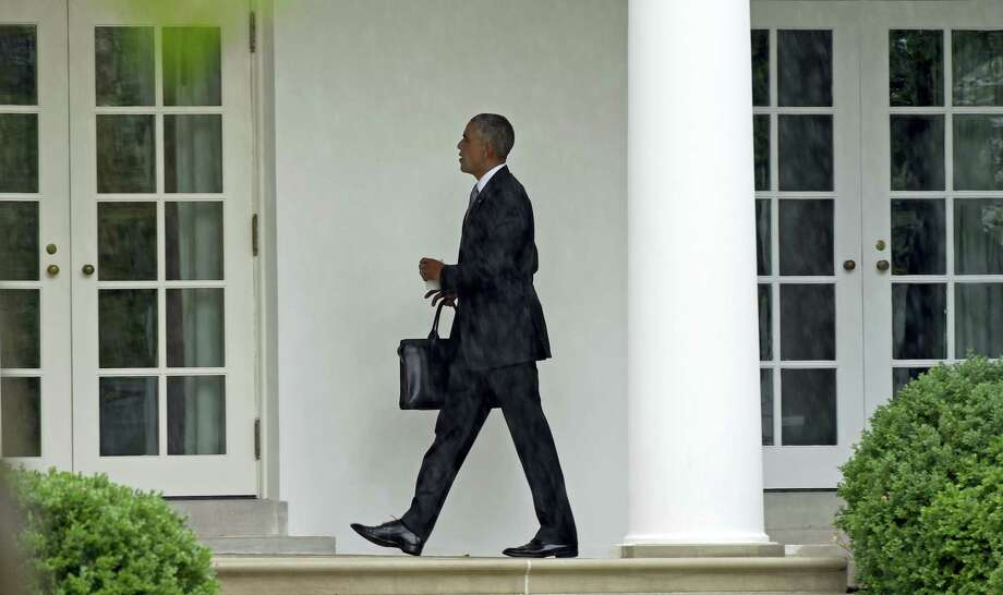 President Barack Obama walks along the Colonnade of the White House in Washington on June 21, 2016, after returning from Walter Reed National Military Medical Center where he visited with injured troops. Photo: AP Photo/Susan Walsh   / Copyright 2016 The Associated Press. All rights reserved. This material may not be published, broadcast, rewritten or redistribu