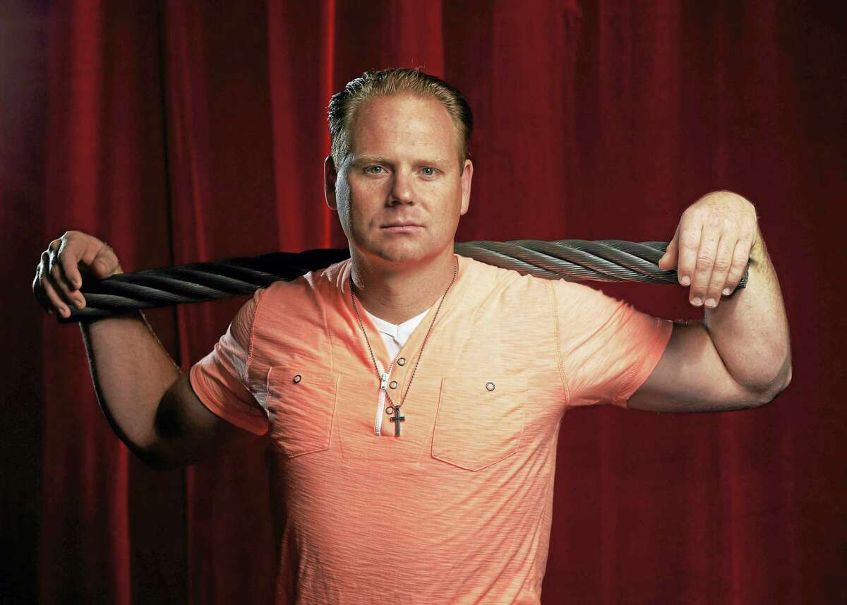 Nik Wallenda poses for a photograph with a piece of the high wire he used to walk over Niagara Falls.