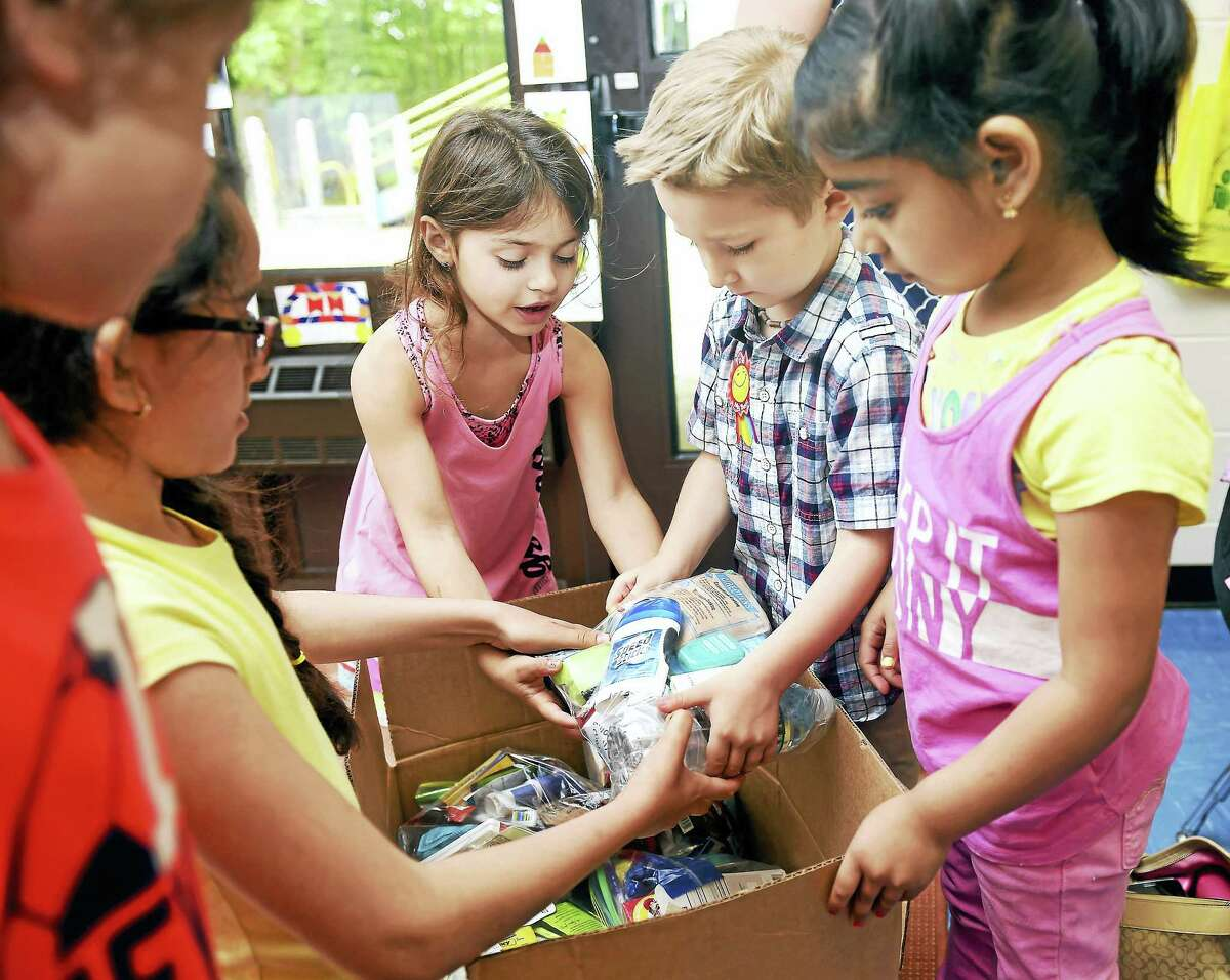 Kindergarten classmates help Jeremy Gagne, second from right, load Blessing Bags into boxes at West Woods School in Hamden Friday. The Blessing Bags are for homeless veterans.