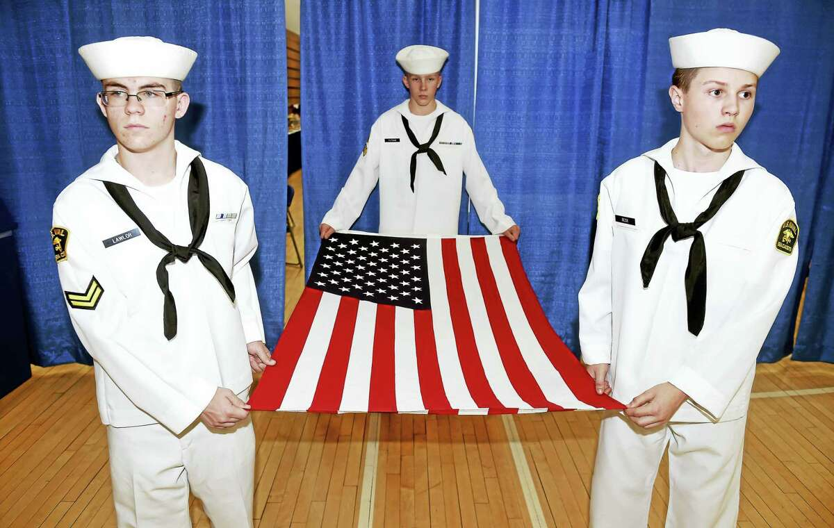 Left to right, U.S. Naval Sea Cadets Sean Lawlor, Roman Putnam and Kasey Beck prepare to carry the flag for folding at the closing ceremony of the Hamden Veterans Awareness Day at Quinnipiac University in Hamden Friday.