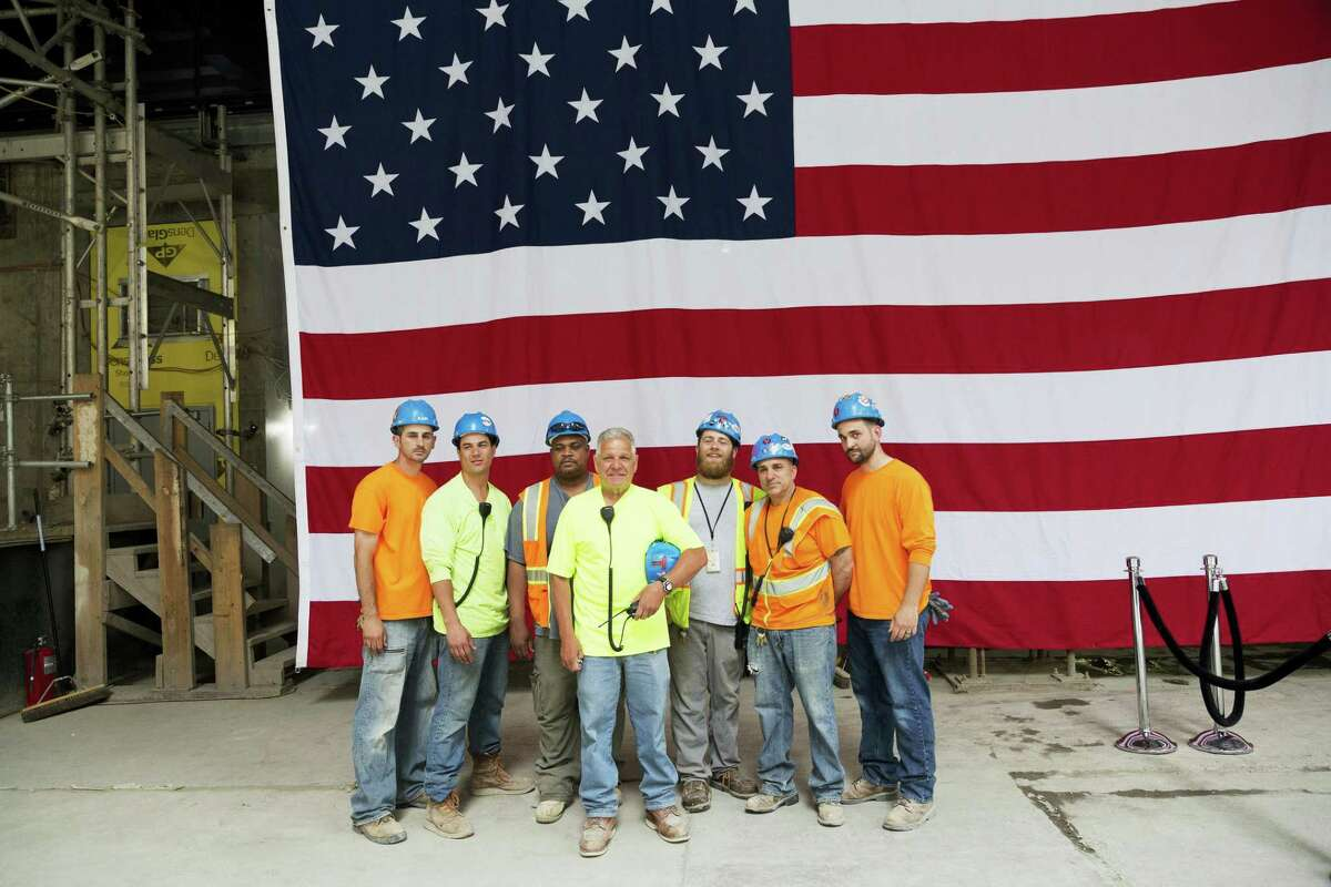 Construction workers pose for photos in front of the United States flag before a topping off ceremony for 3 World Trade Center on June 23, 2016 in New York. It's one of three new skyscrapers that replace the twin towers destroyed almost 15 years ago.