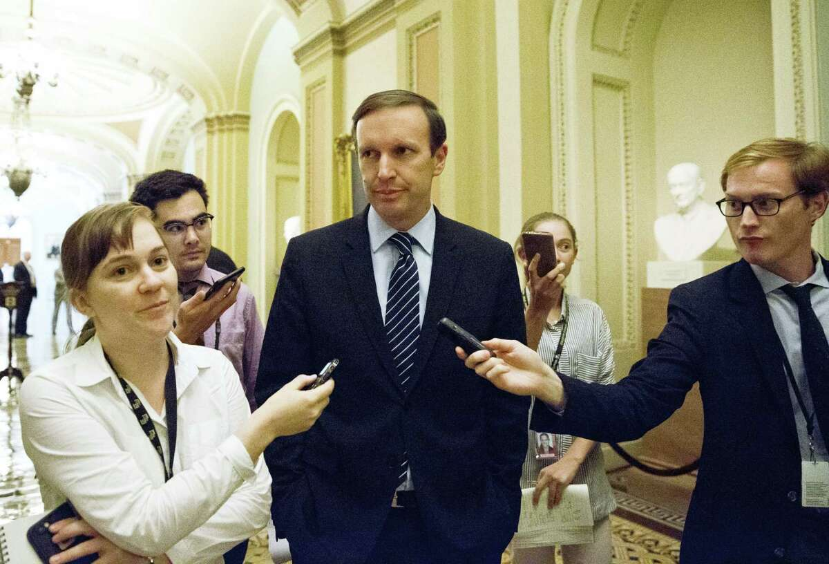 Sen. Chris Murphy, D-Connecticut, center, talks with reporters after leaving the Senate floor Monday. A divided Senate blocked rival plans to curb guns, eight days after the Orlando mass shooting.