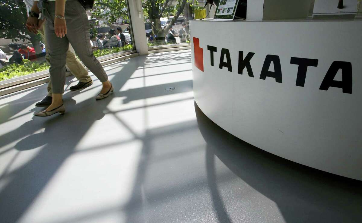 Visitors walk by a Takata Corp. desk at an automaker's showroom in Tokyo.