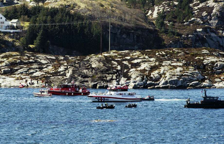 A search and rescue vessel patrols off the island of Turoey, near Bergen, Norway, as emergency workers on the shoreline attend the scene after a helicopter crashed believed to be have 13 people aboard, Friday April 29, 2016.  The helicopter carrying around 13 people from an offshore oil field crashed Friday near the western Norwegian city of Bergen, police said. Many are feared dead. Photo: Marit Hommedal/NTB Scanpix Via AP    / NTB Scanpix