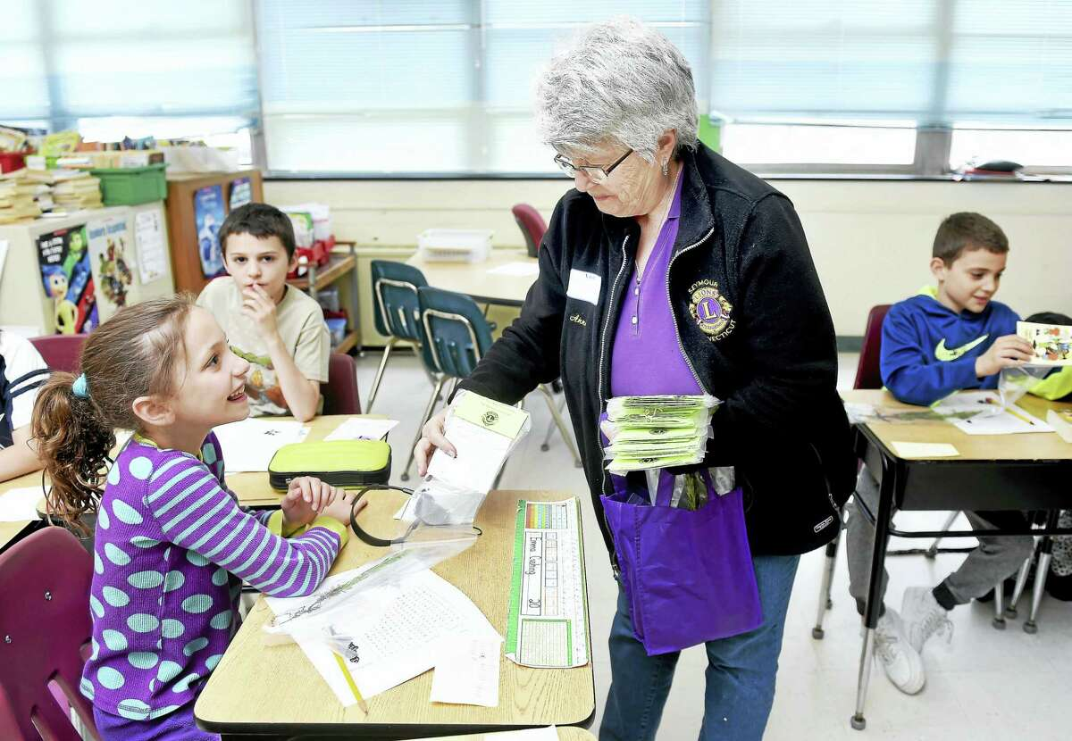Anne Barton, center, of the Seymour Lions Club hands out pine seedlings to fourth-graders at Bungay School in Seymour for Arbor Day Friday. Barton is on the board of directors for the Seymour Lions Club.
