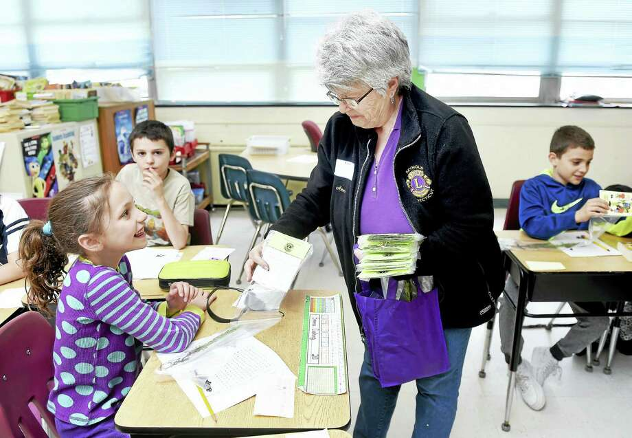 Anne Barton, center, of the Seymour Lions Club hands out pine seedlings to fourth-graders at Bungay School in Seymour for Arbor Day Friday. Barton is on the board of directors for the Seymour Lions Club. Photo: Arnold Gold — New Haven Register