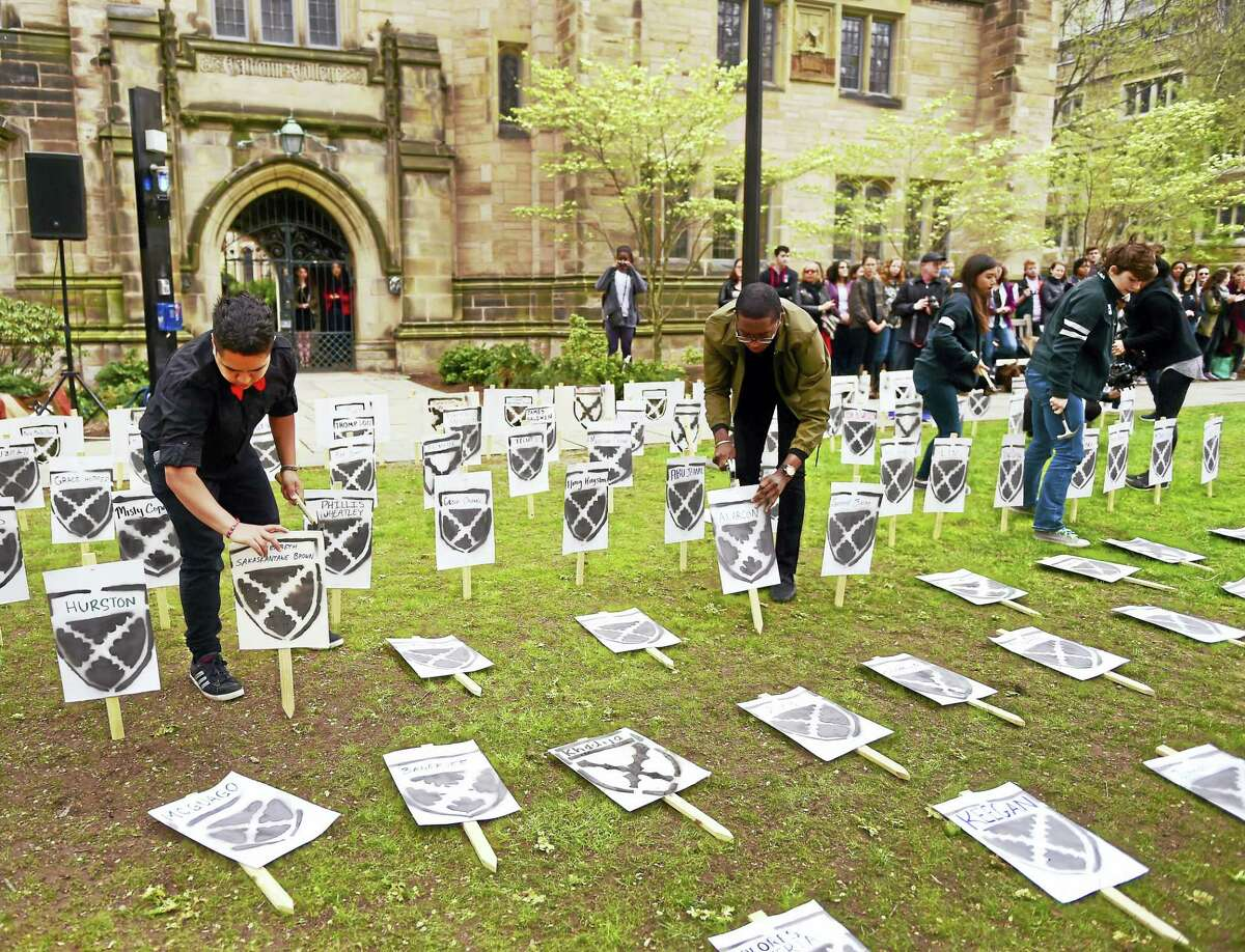 Yale University undergraduate Nicholas Aromoyo, left, an organizer of a mock renaming ceremony Friday for Calhoun College, hammers down a plaque at Cross Campus in front of Calhoun College with a suggested name.