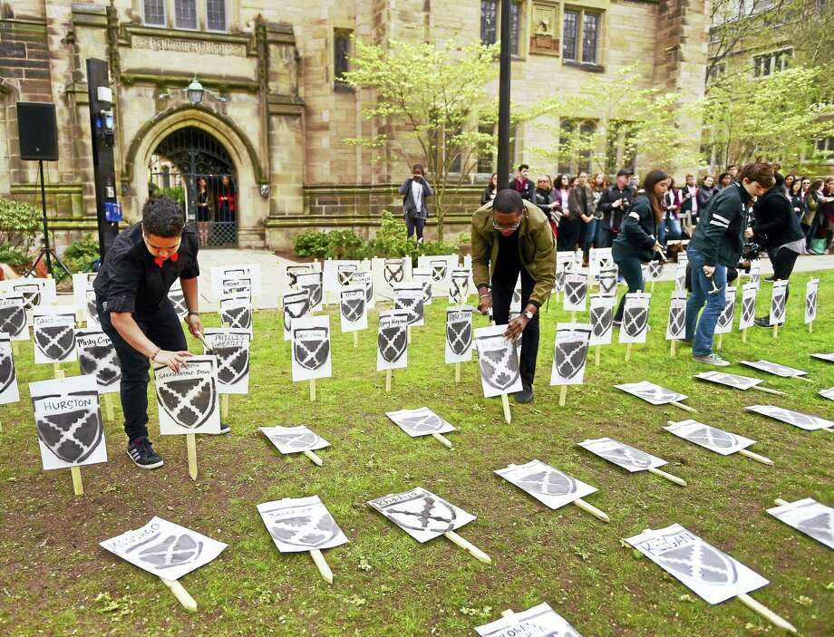 Yale University undergraduate Nicholas Aromoyo, left, an organizer of a mock renaming ceremony Friday for Calhoun College, hammers down a plaque at Cross Campus in front of Calhoun College with a suggested name. Photo: Peter Hvizdak — New Haven Register   / ©2016 Peter Hvizdak