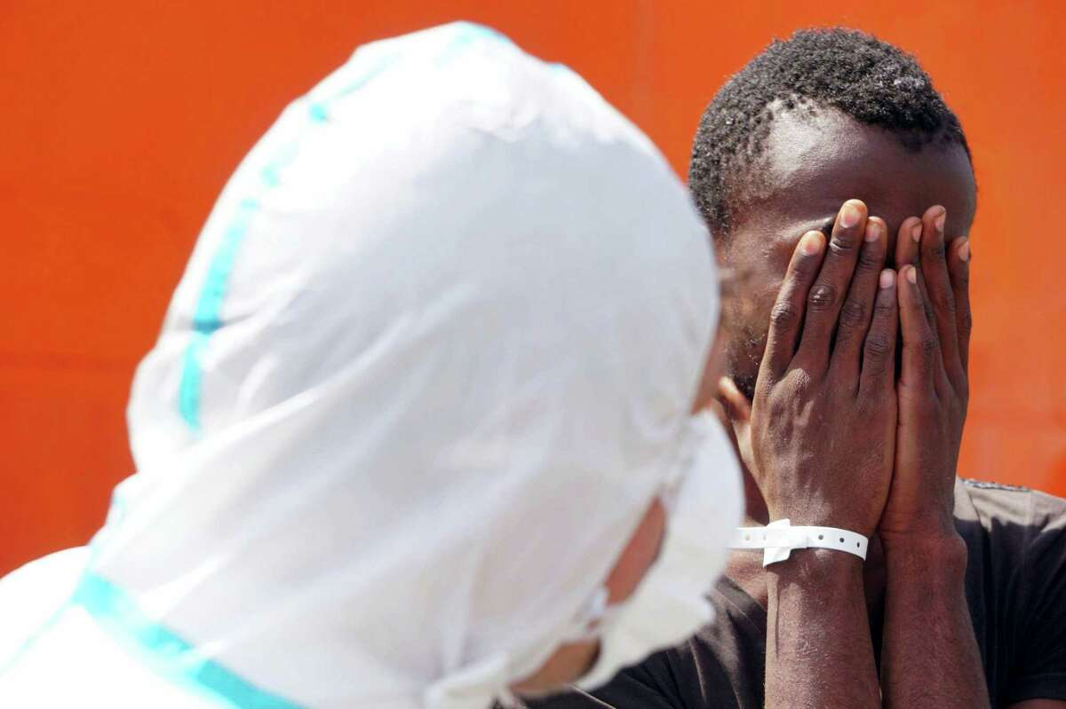 A man covers his face after disembarking from the Norwegian ship Siem Pilot, at the Salerno harbor, Italy, Thursday, May 26, 2016. Rescue operations off Libya's coast have increased in recent weeks amid calm seas and warm weather conditions that encourage Libyan-based smugglers to crowd hundreds of would-be refugees onto unseaworthy boats for the trip to Europe.