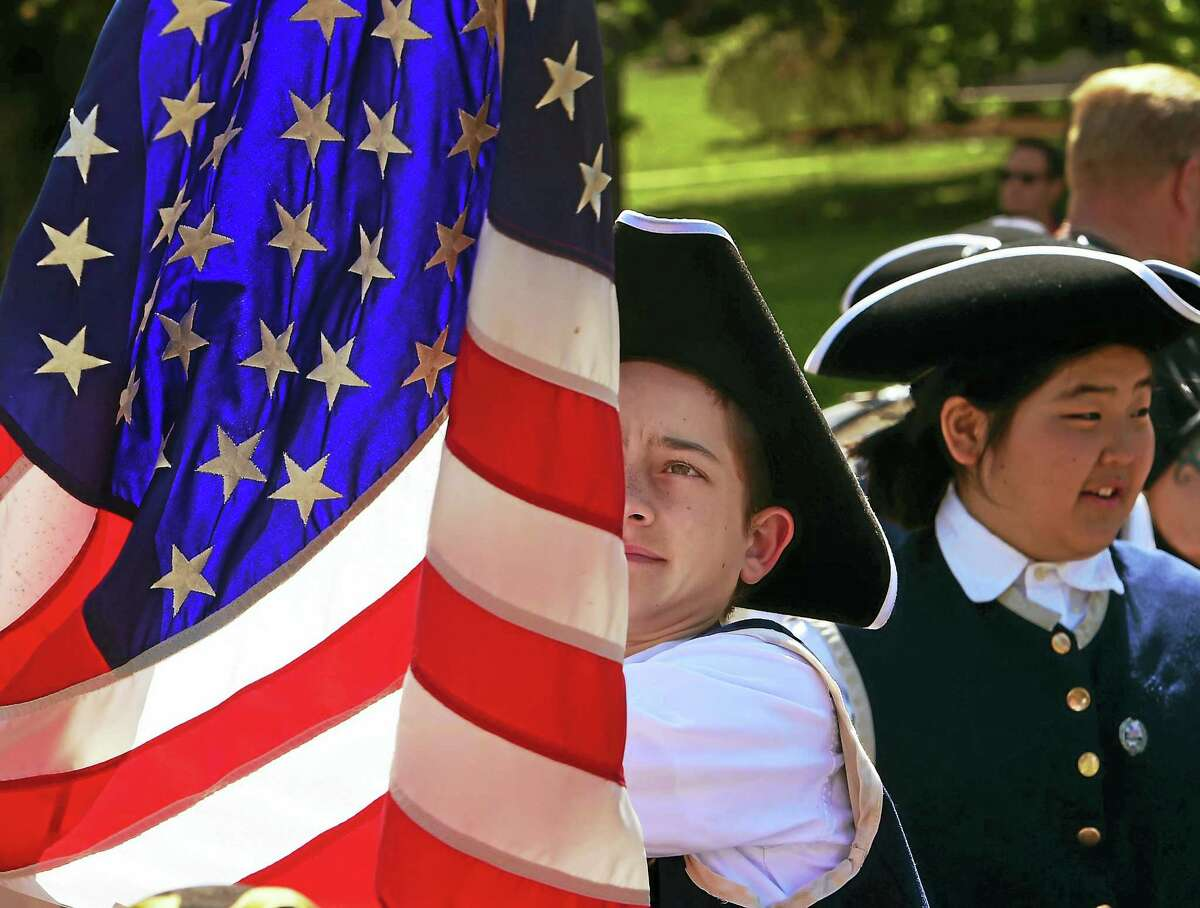 Tucker Sutherland, 12, of the St. Mary's School Fife and Drum Corps of Branford, straightens the American Flag before the start of the Branford Memorial Day Parade in 2015.