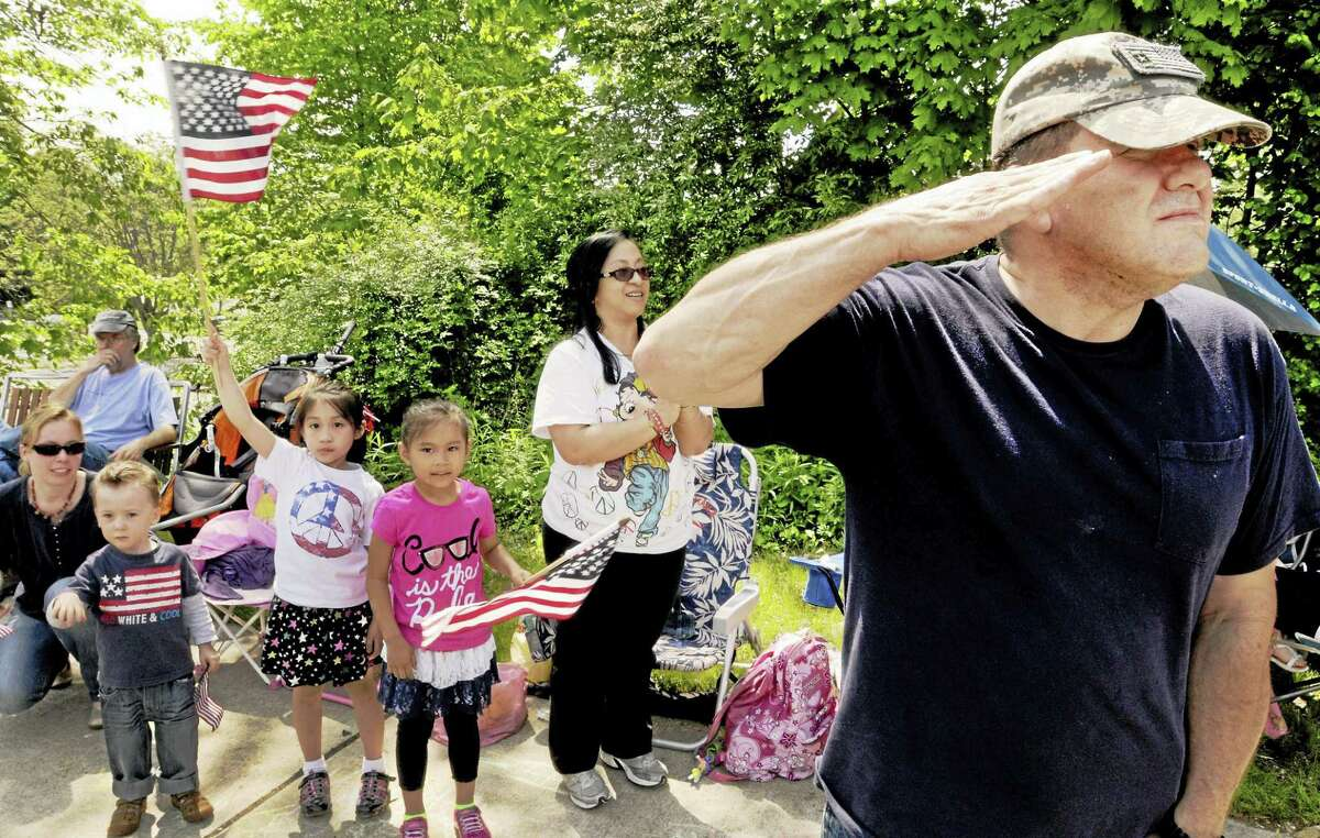 Sgt. William Rodriquez, U.S. Army Retired salutes the flag as it passes by at Hamden's parade last year.